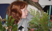 Meisje maakt bloemstuk tijdens kerstviering